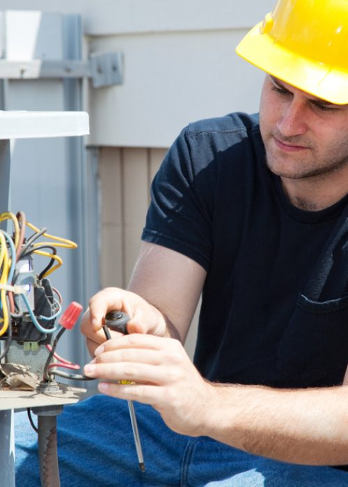 Young repairman fixing an industrial air conditioning compressor.
